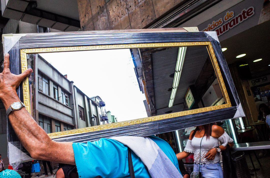 Man carrying a mirror on his shoulder